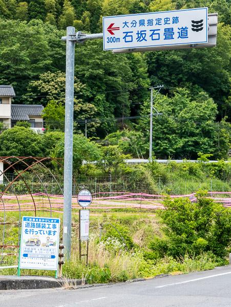 バス停の真上に「大分県指定史跡 300m 石坂石畳道」と道路案内板がある